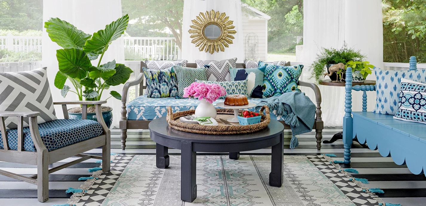 Boho furniture stacked against clean minimalist walls for an enclosed patio create an elegant ambience ©Better Homes