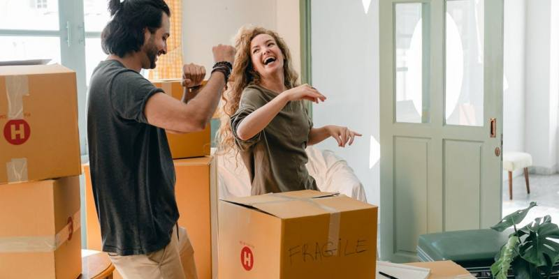 Cheerful laughing couple in casual clothes having fun and dancing together while unpacking carton boxes after moving into new contemporary apartment
